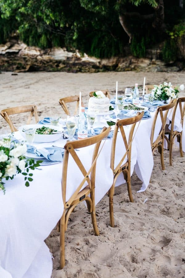 Cross back wooden chairs, at long table with linen, set up for party on the beach - tall photo
