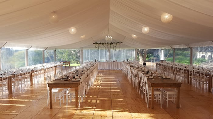 rows of rustic tables in marquee