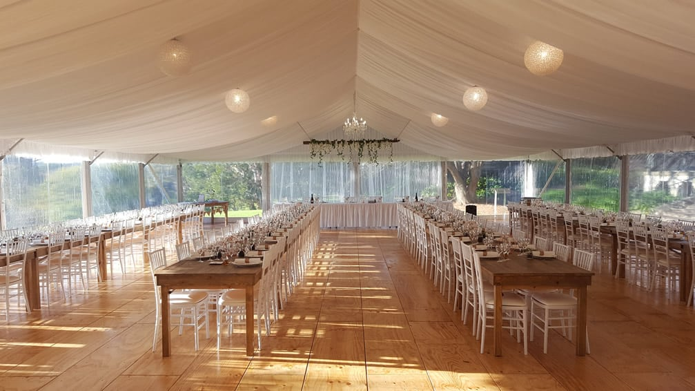 rustic tables and tiffany chairs in marquee