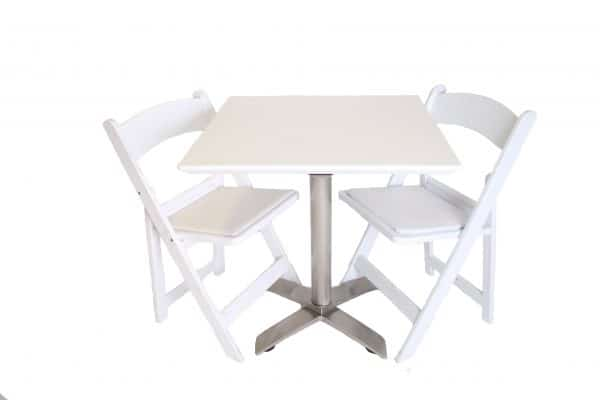 White cafe table with white folding chairs