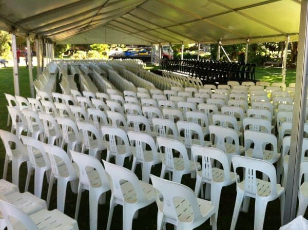 Olsens memorial service- white plastic chair set up under a marquee