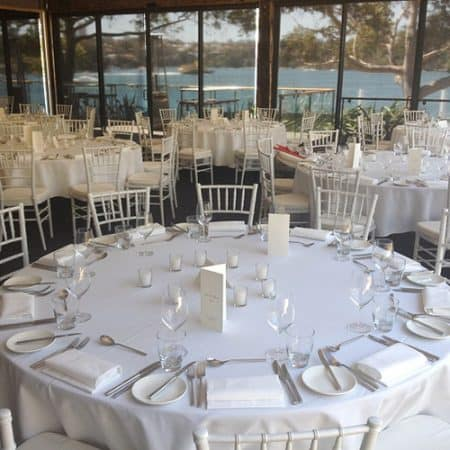 White table linen on round table with white tiffany chairs