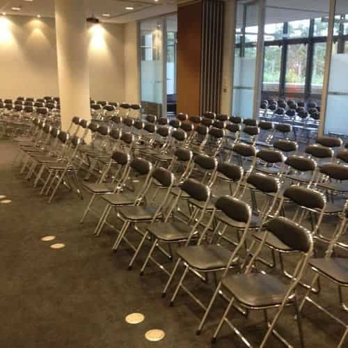 Rows of chrome folding chairs at corporate meeting North Sydney