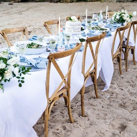 Cross back wooden chairs, at long table with linen, set up for party on the beach