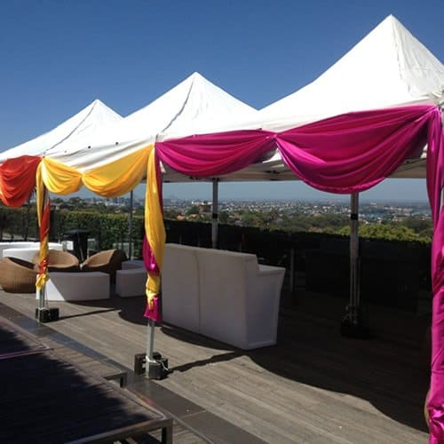 3 Shelters decorated with drapes on balcony with glow bars