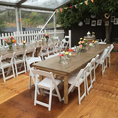 Wedding chairs at rustic table in marquee