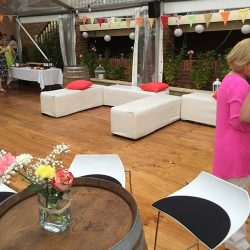 White ottoman benches in marquee