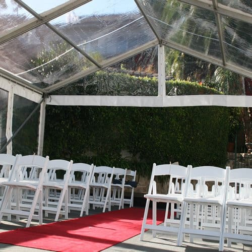 rows of folding wedding chairs with red carpet in marquee