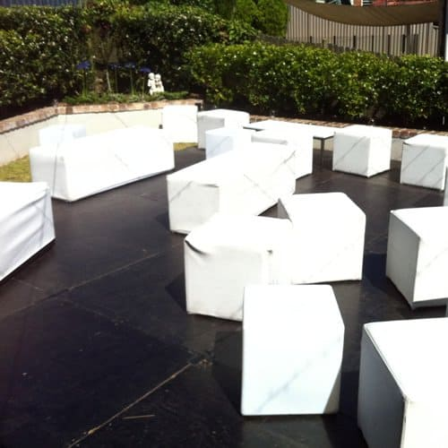 white ottoman cubes and benches in backyard party