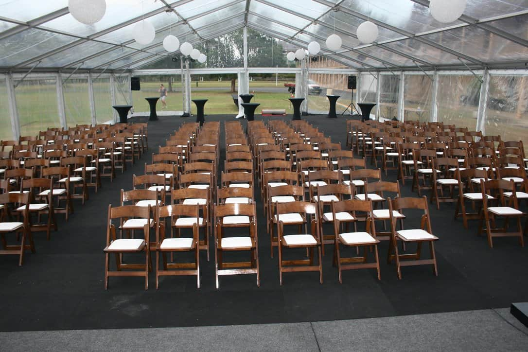 A clear marquee set up with rows of of wooden folding chairs