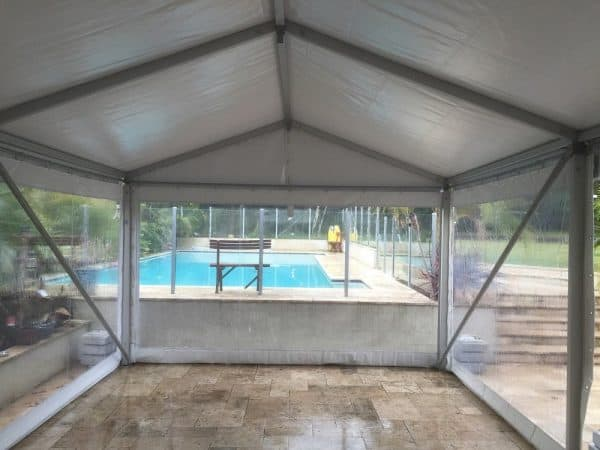 marquee on pavers clear walls facing pool