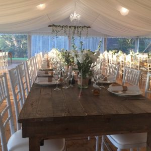 White tiffany chairs set at rustic tables for wedding dinner