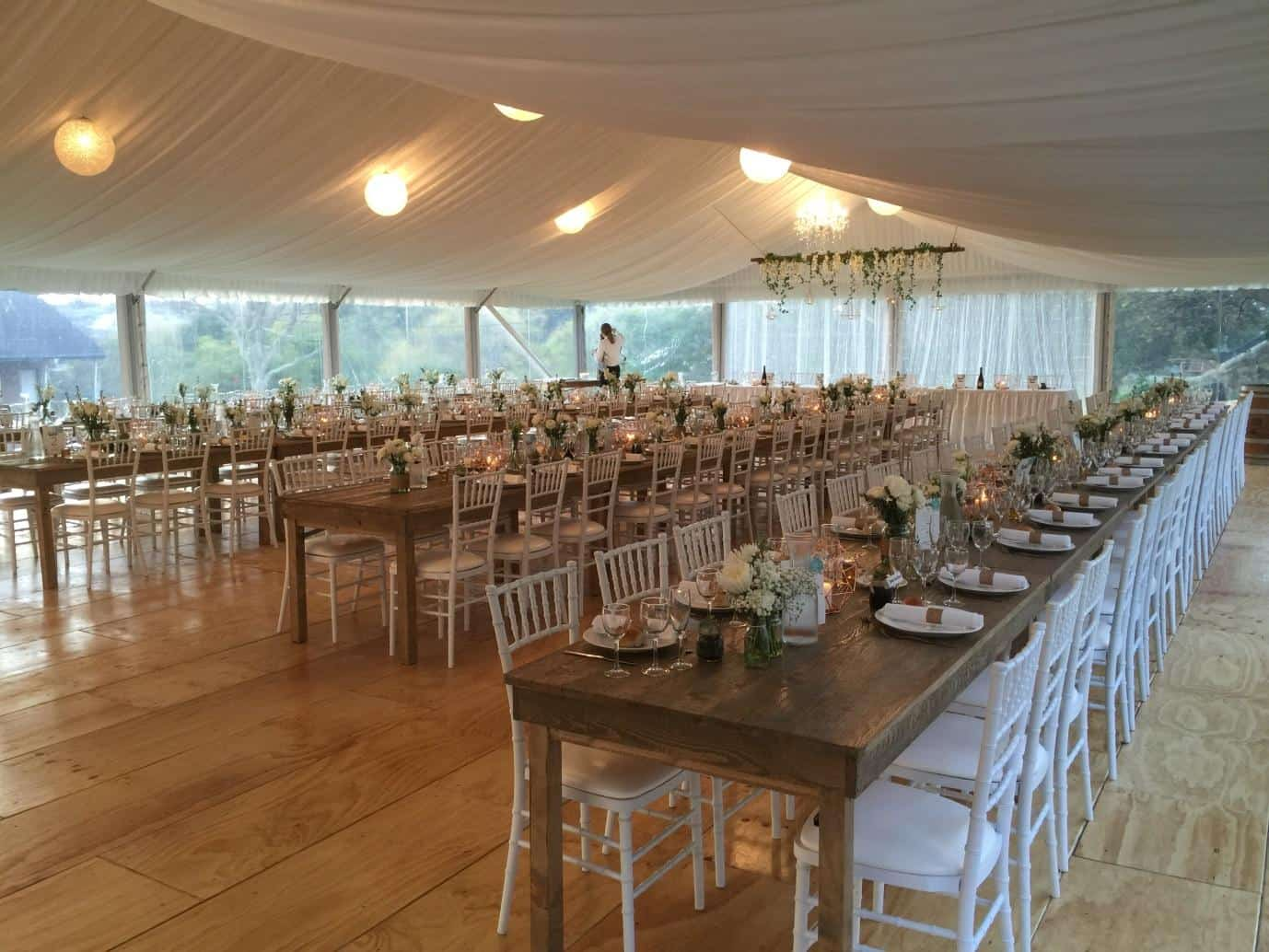 Tables and chairs inside a white draped marquee - a white and rustic theme for a country wedding