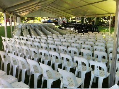 White stackable chairs under a marquee in Longeuville