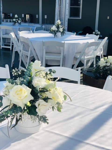 Round tables, white padded chairs, white linen and roses set up for a small birthday function